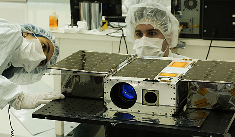 Electrical Test Engineer Esha Murty (left) and Integration and Test Lead Cody Colley (right) prepare the ASTERIA spacecraft for mass properties measurements in April 2017 prior to spacecraft delivery. Image: NASA