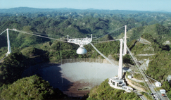 The famous Arecibo Observatory perched in the Puerto Rican hills faces imminent deconstruction amid safety fears over the crumbling structure. Image: NSF