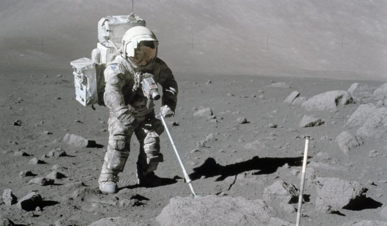 NASA astronaut Harrison Schmitt uses scoop to retrieve lunar samples during the Apollo 17 mission in 1972. The dust is clearly evident over the vast majority of his suit. Image: NASA