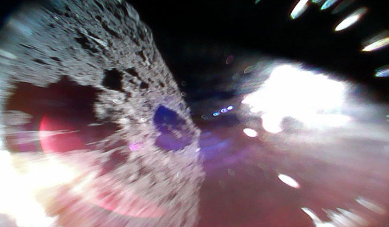 Rover in motion. Image captured by Rover-1A on 22 September while moving (during a hop) on the surface of Ryugu. The left-half of the image is the asteroid surface. The bright white region is due to sunlight. Image: JAXA