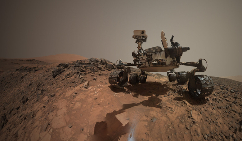 A low-angle self-portrait of NASA's Curiosity Mars rover drilling into a rock target called