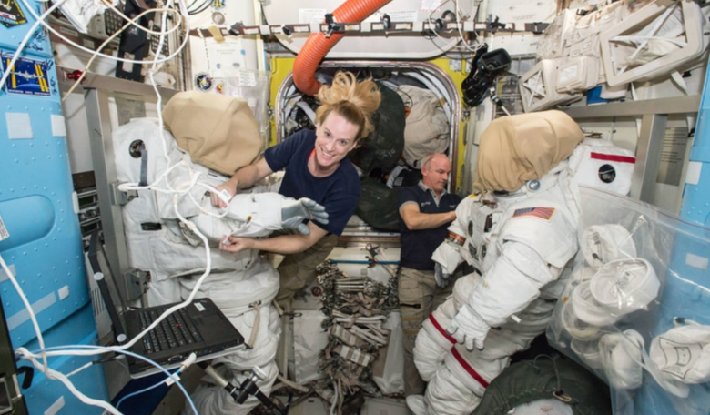 Expedition 48 crew members Kate Rubins (left) and Jeff Williams (right) of NASA outfit spacesuits inside of the Quest airlock aboard the International Space Station. Credit: NASA
