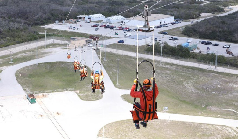 Engineers test and evaluate the Emergency Egress System (EES) as they ride in seats attached to slide wires at Space Launch Complex 41. Credit: NASA/Leif Heimbold