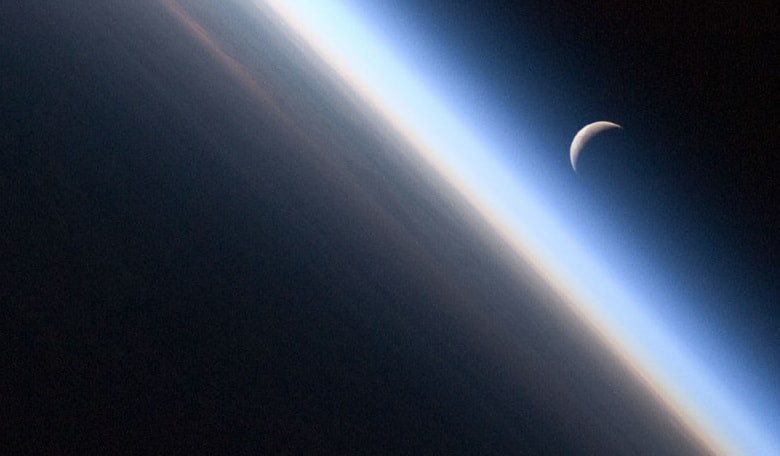 A setting crescent Moon and the thin line of Earth's atmosphere viewed from the International Space Station