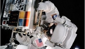Spacewalking astronaut installing a tray supporting numerous material samples at the International Space Station.