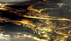 The setting sun glints off the Amazon river and numerous lakes in its floodplain in this photograph from the ISS.