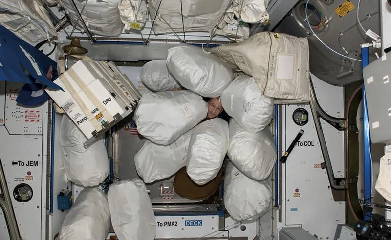 The face of astronaut Don Pettit peers out from rubbish stowage bags in the Harmony node of the ISS