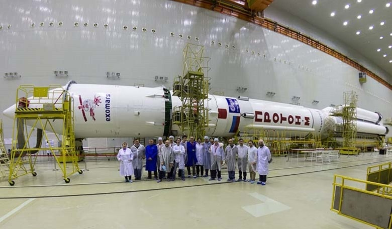 Some of the team at Baikonur who are preparing the ExoMars 2016 spacecraft for launch, pictured in front of the Proton rocket.