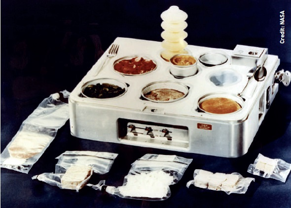 The Skylab food heating and serving tray from 1970, complete with food, drink, and utensils.