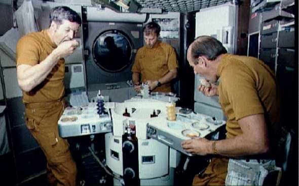 A Skylab crew eat from their trays at the Raymond Loewy-designed table in 1973. L-R: Joseph P. Kerwin, Paul J. Weitz and Charles Conrad Jr.