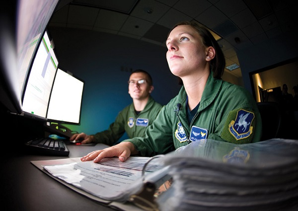 Airman Ashley Risk (foreground) and Airman 1st Class Jasper Platt oversee a satellite system procedure at Schriever Air Force Base, Colorado. They are space ground link operators with the 4th Space Operations Squadron